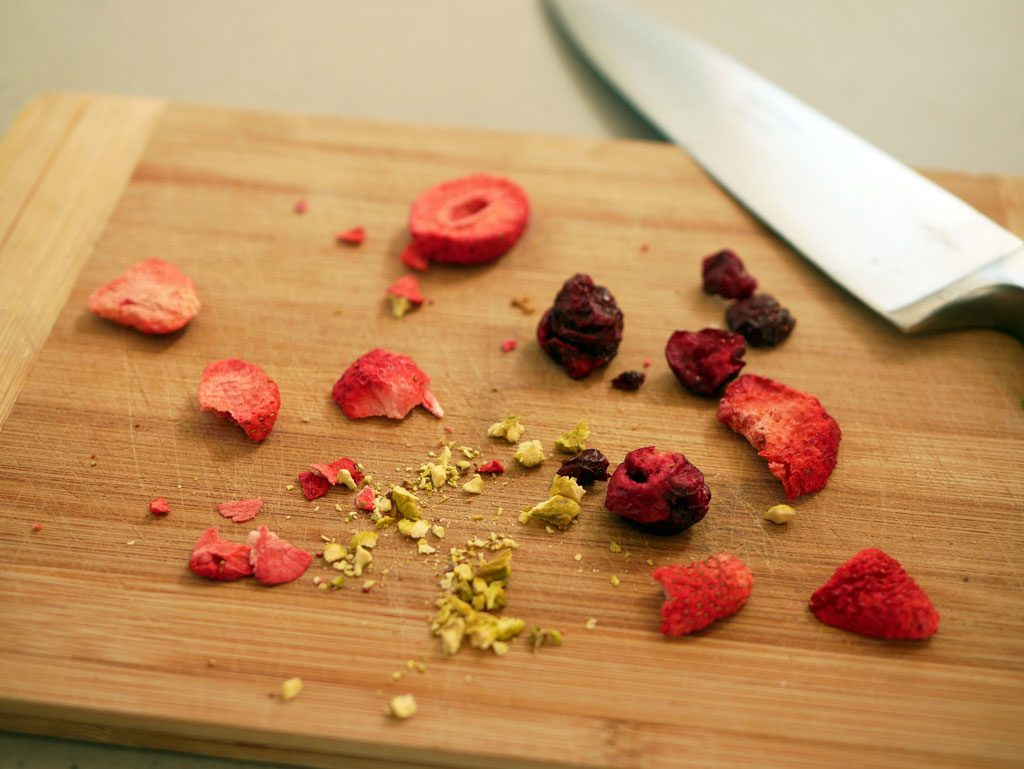 Cutting red dried fruit and pistachios