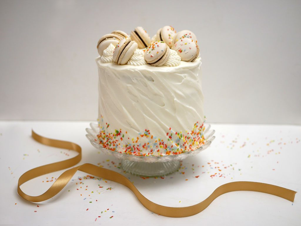 Chocolate cake with whipped cream frosting and macarons